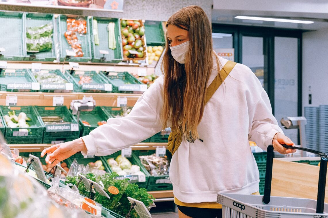 A woman chooses vegan options at a grocery store